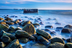 Sea scape with rocks. And Wooden pier or jetty remains, long exposure Stock Photography