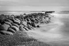 Sea scape with rocks. And Wooden pier or jetty remains, long exposure, black and white Stock Photography