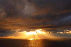 Sun rays through dark cloud layer over ocean Royalty Free Stock Photos