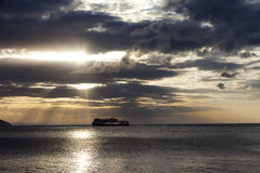 Sea with sea boat and gray sky with sun at sunset Royalty Free Stock Images
