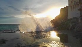 Sea that shatters with spray against the sun stock photos