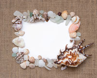 Sea shell border on burlap texture Stock Image