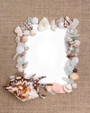 Sea shell border on burlap texture Stock Photo