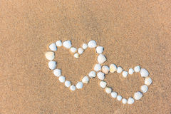 Sea shell hearts on the sand beach Royalty Free Stock Images