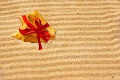 Sea Shell with red ribbon and gold sand Royalty Free Stock Photo