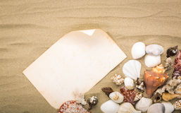 Sea shells on beach sand with old paper. Summer Stock Photography