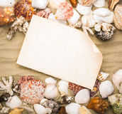 Sea shells on beach sand with old paper. Royalty Free Stock Images