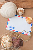 Sea shells and envelope. Sea shells and air mail envelope on brown fabric background and wood Stock Photography