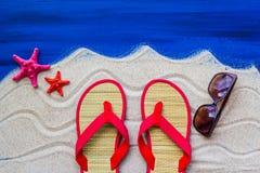 Sea shells flip flops beach sand Stock Images