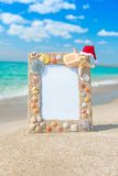 Sea shells frame with christmas hat against sea beach Royalty Free Stock Photos