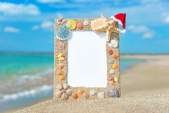 Sea shells frame with christmas hat against sea beach Stock Images