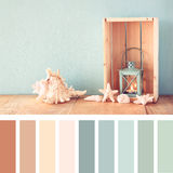 Sea shells and lantern on wooden table. vintage filtered image. nautical lifestyle concept. with palette color swatches Stock Image