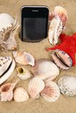 Sea shells and mobile phone Royalty Free Stock Photography
