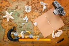 Sea shells, an old camera, a compass and accessories for snorkelling lie on a vintage map. Copy space. View from above. Travel Planning stock image