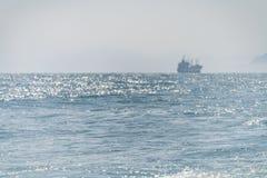 Sea ship sails. Along the shore at sun light stock images
