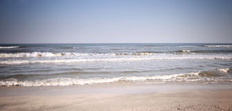 Sea shore. Dreamy sea shore with blue waves washing sandy beach - copy space stock image