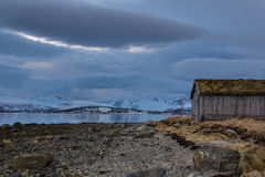 Sea shore abandoned wooden house in a cloudy day Stock Photography