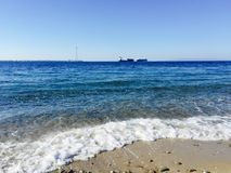 Sea shore. And beach with container ships in the background Royalty Free Stock Photo