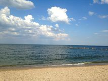 Sea shore and the blue sky with white clouds. Stock Image