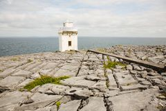 Irish coastline, sea and horizon, broken rock ground with light house. Sea shore, flat, cracked stone surface with steps leading to a white light house Royalty Free Stock Image