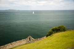 Sea shore, grass covered hill side and old stone wall with window outdoors, Ireland Royalty Free Stock Images