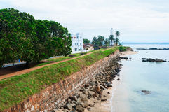 Sea shore with high wall and white lighthouse Royalty Free Stock Photo