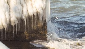 Sea shore in ice. Rocky sea shore in the ice and with big icicles Royalty Free Stock Photos