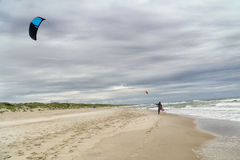 Sea shore with kite surfer walking along coastline Stock Photos