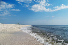 Sea shore. A nice transition from the sandy beach to waves washing the shore and the blue color of the sea in a sunny day Stock Photography