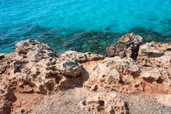 Sea shore with rocks and clear transparent sea water. Natural marine background. Blue ocean wallpaper, sea wave on. Sunshine day. Crystal clear water and orange royalty free stock images