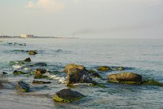 Sea shore with rocks, on the horizon beach with buildings stock photos