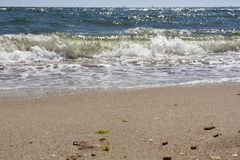 Rolling waves on a sandy beach in a seaside resort stock photos