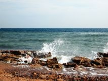 Sea shore, small wave surf and sea foam. Tranquil landscape in nature Royalty Free Stock Images