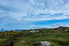 A trail on the sea bay. On the sea shore there is a green meadow with gray boulders; a trail on the sea bay above which there is a beautiful cloudy sky stock photography
