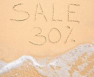 The word Sale 30% written in the sand on beach Stock Photos