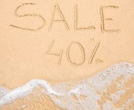 The word Sale 40% written in the sand on beach Stock Photos