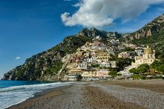 Sea shore vista under blue skies with fluffy white clouds. Amalfi, Italy Stock Photo