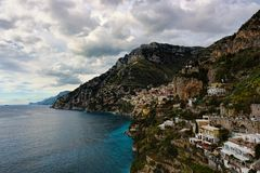 Sea shore vista under blue skies with fluffy white clouds. Amalfi, Italy Royalty Free Stock Photography