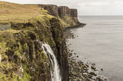 Sea shoreline with Kilt Rock in the background. Sea shoreline with Mealtfalls in foreground and Kilt Rock in the background, Skye Island, Scotland Stock Photography