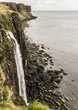 Sea shoreline with Kilt Rock in the background. Sea shoreline with Mealtfalls in foreground and Kilt Rock in the background, Skye Island, Scotland Royalty Free Stock Photography