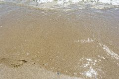 Sea shoreline with waves, sandy beach on a clear sunny day, close-up nature abstract background. The sea shoreline with waves, sandy beach on a clear sunny day stock photos