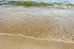 Sea shoreline with waves, sandy beach on a clear sunny day, close-up nature abstract background. The sea shoreline with waves, sandy beach on a clear sunny day stock photo