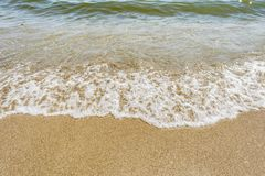 Sea shoreline with waves, sandy beach on a clear sunny day, close-up nature abstract background. The sea shoreline with waves, sandy beach on a clear sunny day royalty free stock photo