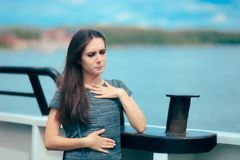Sea sick woman suffering motion sickness while on boat. Suffering girl traveling on water and feeling fearful and unwell royalty free stock image