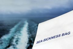 Sea Sickness Bag Against Stormy Ocean. Sea sickness bag against a stormy ocean background with wake from a ship and a shallow depth of field Royalty Free Stock Photography