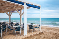 Sea side bar with wooden floor and metal armchairs Stock Photos