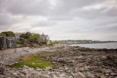 Homes along rocky coast of Maine near Portland. Sea side Houses on rocky shores overlooking Atlantic Ocean near Port;and Maine at low tide royalty free stock image