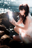 Sea Side SOS. Beautiful Young Woman With Dress On Sunlit Rocks Holds A Cry For Help In The Form Of A Sea Side SOS Sent From A Castaway Lost Out At Sea Stock Images