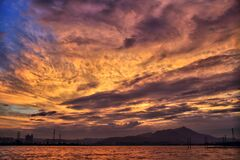 Sea and Silhouette of Mountain Under Orange Sky during Golden Hour Royalty Free Stock Photos