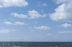 Sea and sky. Blue sky and fluffy white clouds with sea at base Stock Photo